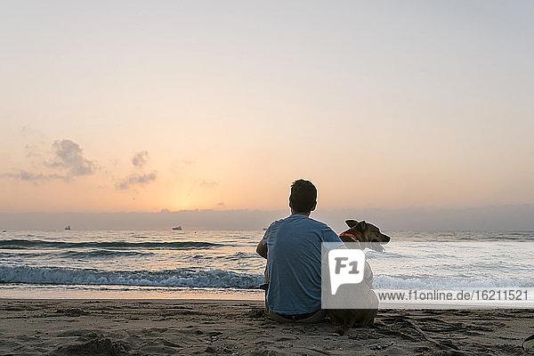 Man sitting with his dog enjoying dawn at beach