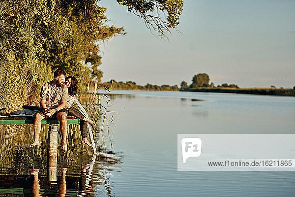 Paar  das sich im Wasser spiegelt  sitzt auf einem Steg an einem See Paar, das sich im Wasser spiegelt, sitzt auf einem Steg an einem See