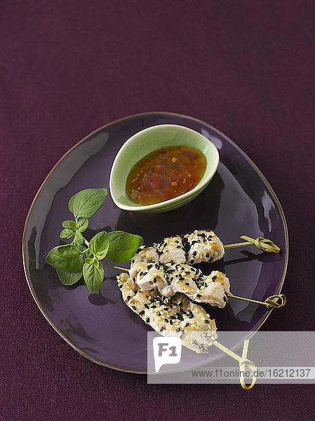 Hähnchenspieße im Teller mit Chilisauce  Nahaufnahme