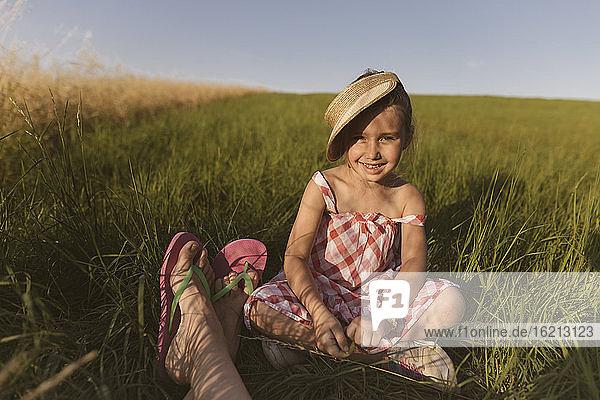 Lächelndes Mädchen sitzt mit Mutter auf dem Land gegen den klaren Himmel bei Sonnenuntergang