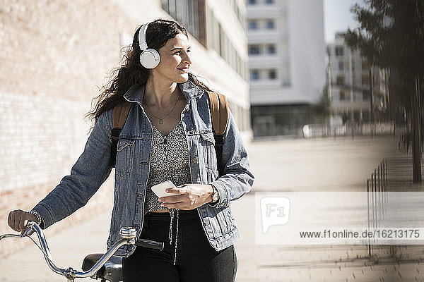 Junge Frau hört Musik und schaut weg  während sie mit dem Fahrrad in der Stadt steht