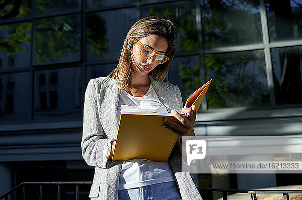 Businesswoman taking with note book outside office building