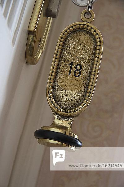 Hotel key in a room door  close-up