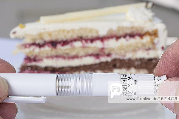 Deutschland  Freiburg  Älterer Mann mit Insulin in der Hand und einem Stück Kuchen im Hintergrund