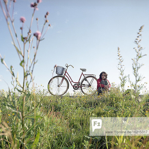 Finland  Young woman sitting in meadow