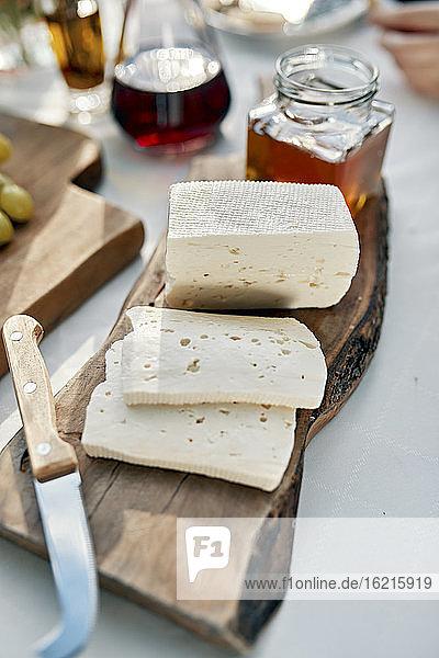 Weichkäse in Scheiben geschnitten auf einem Stück Holz Weichkäse in Scheiben geschnitten auf einem Stück Holz