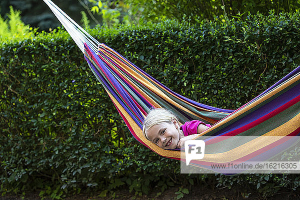 Smiling girl relaxing in colorful hammock at garden