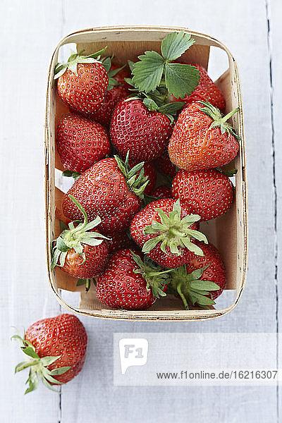 Kiste mit Erdbeeren auf Holztisch  Nahaufnahme