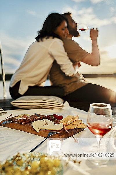 Paar beim Picknick auf einem Steg an einem See bei Sonnenuntergang Paar beim Picknick auf einem Steg an einem See bei Sonnenuntergang