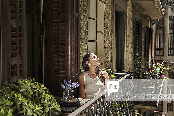 Woman with closed eyes relaxing in balcony