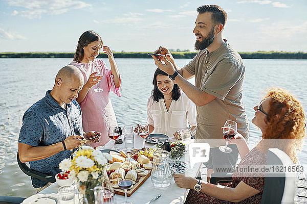 Freunde beim Abendessen an einem See  die ein Smartphone-Foto machen Freunde beim Abendessen an einem See, die ein Smartphone-Foto machen