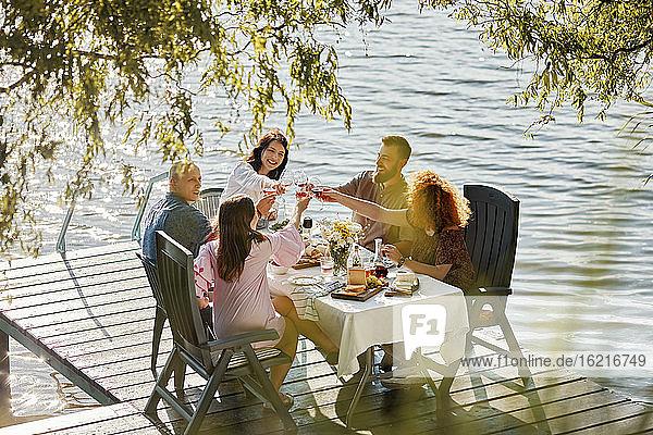 Freunde beim Abendessen auf dem Steg eines Sees stoßen mit Weingläsern an Freunde beim Abendessen auf dem Steg eines Sees stoßen mit Weingläsern an