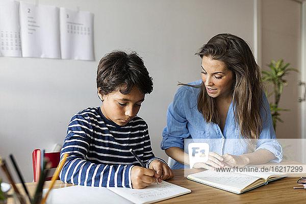 Weiblicher Tutor hilft Jungen beim Schreiben von Hausaufgaben auf dem Tisch zu Hause
