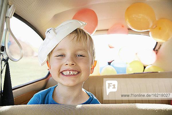 Deutschland  Nordrhein-Westfalen  Köln  Porträt eines Jungen im Auto mit Osterhasenmaske  lächelnd