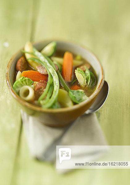 Schüssel mit Suppe  Wurst und Gemüse auf Holztisch  Nahaufnahme