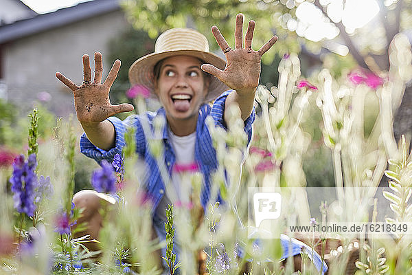 Cheerful young woman showing dirty hands while sitting amidst plants in garden