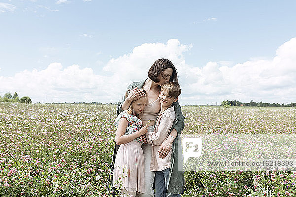 Loving mother embracing children while standing amidst flowers in field against sky