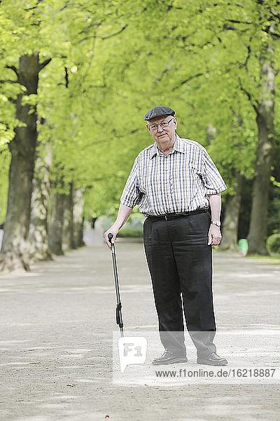 Germany  North Rhine Westphalia  Cologne  Portrait of senior man with walking stick in park