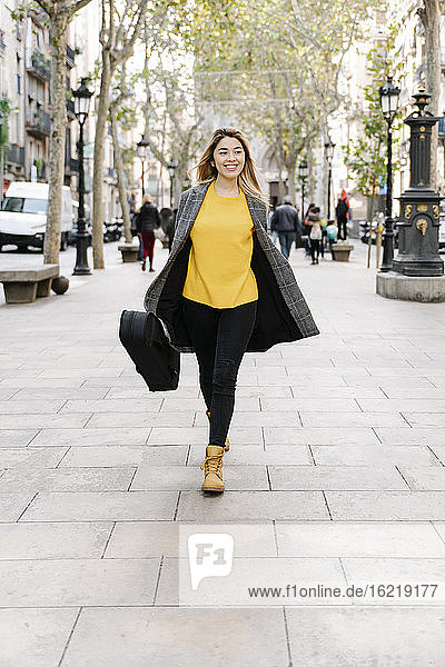 Young woman with violin case walking in city