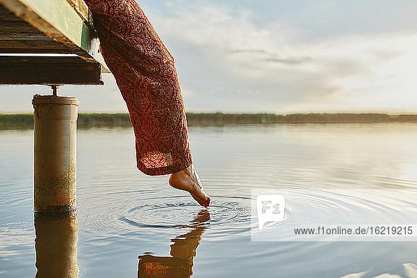 Frau sitzt auf einem Steg an einem See bei Sonnenuntergang und berührt das Wasser mit ihrem Fuß Frau sitzt auf einem Steg an einem See bei Sonnenuntergang und berührt das Wasser mit ihrem Fuß