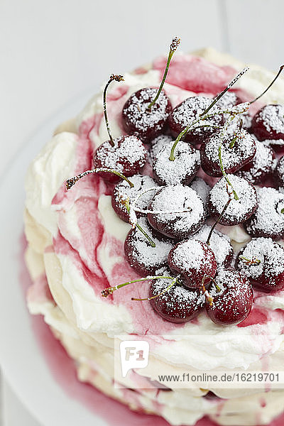 Pavlova with whipped cream  cherries  cherry sauce and icing sugar on cake stand  close up