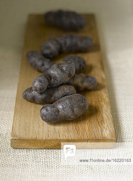 Blauviolette Kartoffeln mit Trüffel de Chine auf dem Schneidebrett