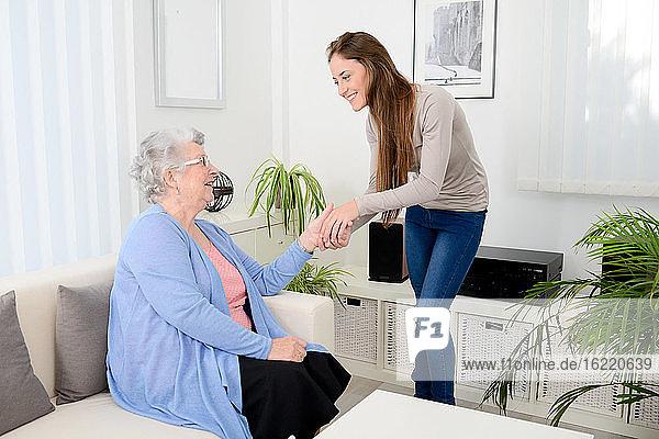 Fröhliches junges Mädchen kümmert sich zu Hause um eine alte Frau