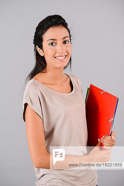 isolierte Studioaufnahme einer fröhlichen jungen Studentin  die lächelt