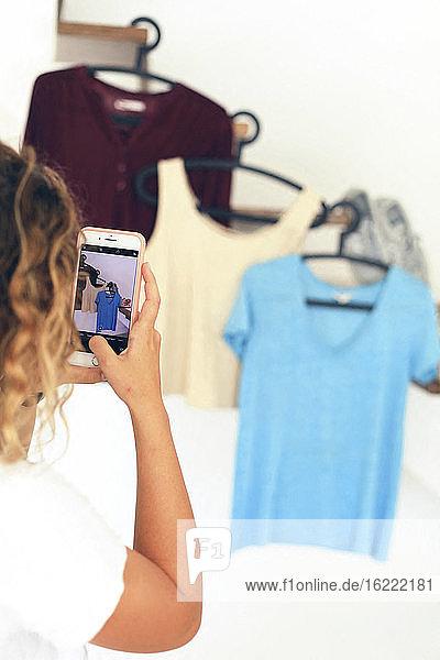 Junger Teenager zu Hause mit einem Smartphone  der die Vinted-App nutzt  um seine Kleidung zu verkaufen