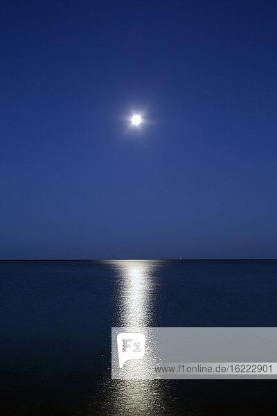 Vollmond in der Morgendämmerung auf dem Meer.
