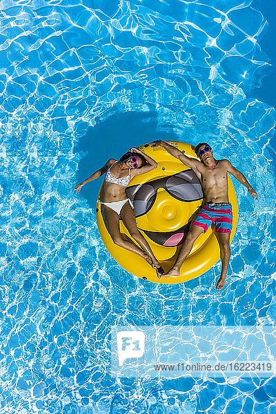 Junges Paar und Smiley-Boje am Pool