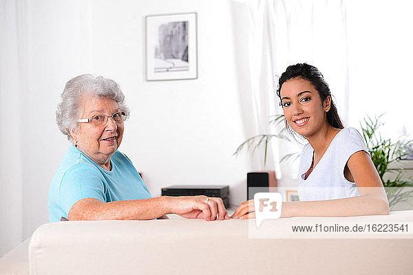 Porträt von zwei Generationen multiethnischer junger und älterer Frauen auf dem Sofa zu Hause