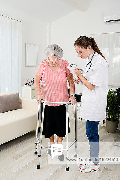 Young doctor checking rehab medical progress to elderly woman at home.