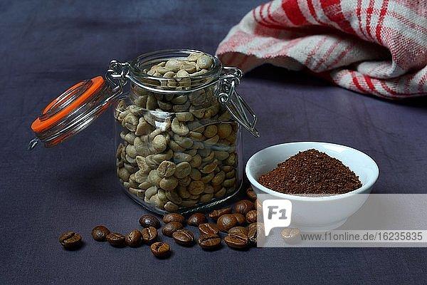Rohkaffee in Glas  geröstete Kaffeebohnen und Kaffeepulver in Schale  Deutschland  Europa