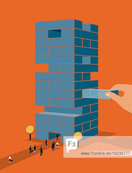Hand entfernt Bausteine aus Büroturm