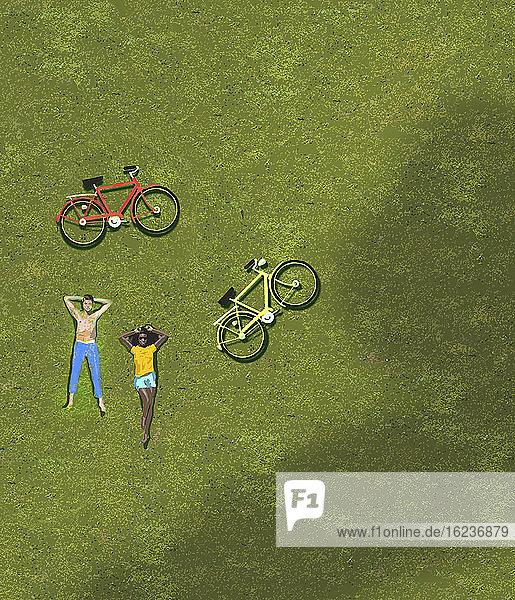 Draufsicht auf ein Paar beim Sonnenbaden auf Gras neben Fahrrädern