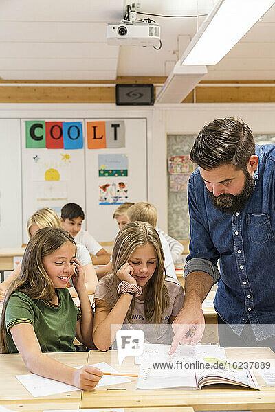 Lehrerin hilft Mädchen im Klassenzimmer