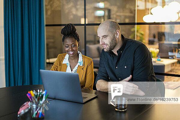 Coworkers using laptop in boardroom