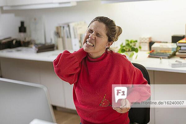 Woman massaging her neck at desk