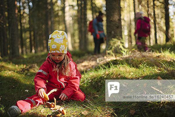 Mädchen sitzt im Wald
