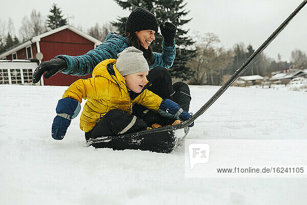 Mother with son on sleigh snow shovel