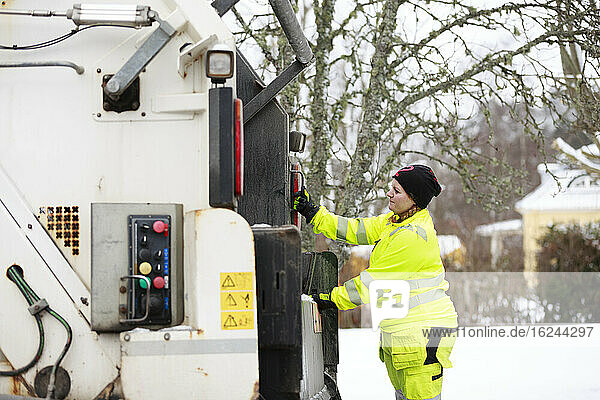 Woman operating garbage truck