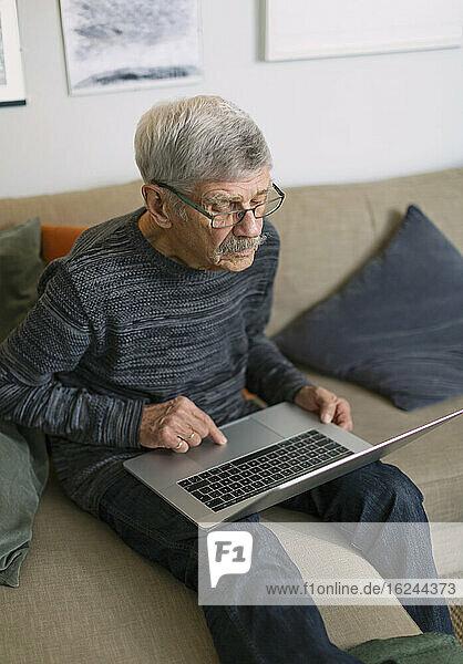 Älterer Mann mit Laptop auf dem Sofa