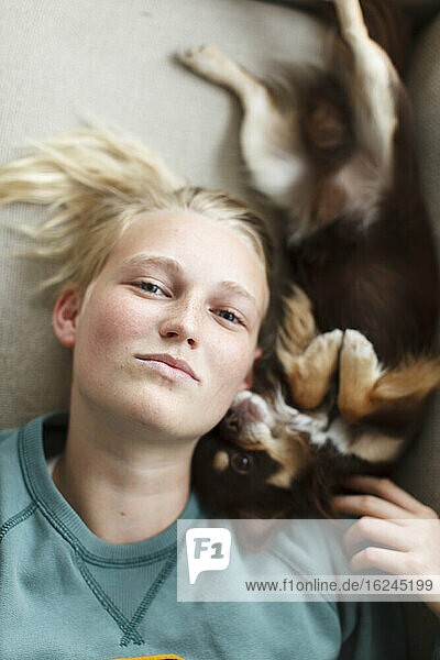 Teenage girl lying on bed with dog