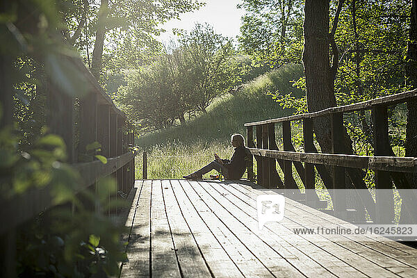 Woman sitting on wooden bridge