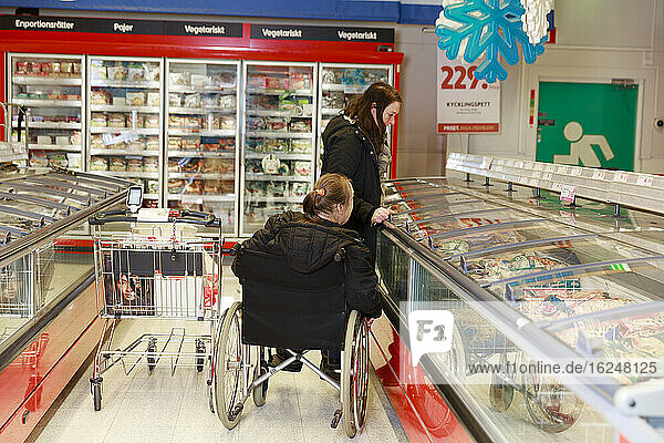 Female carer helping woman with shopping