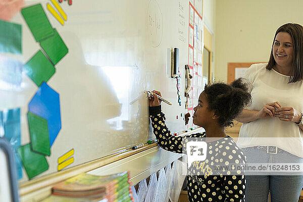 Girl writing on whiteboard in classroom