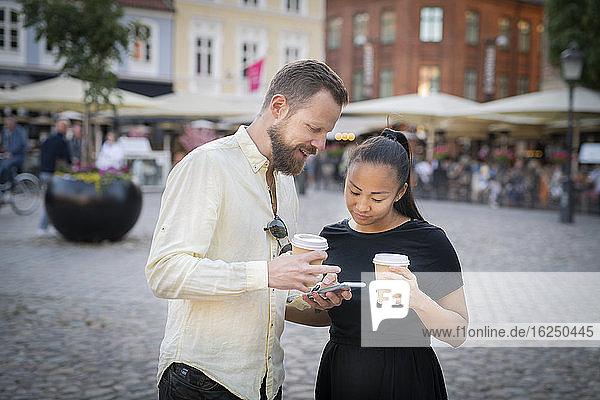 Ehepaar hält Kaffeetassen und schaut auf das Mobiltelefon
