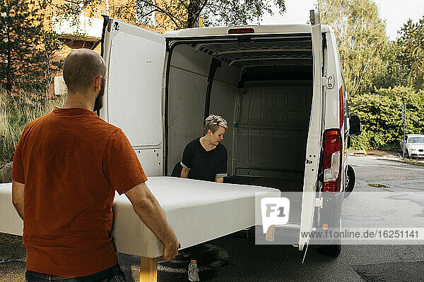 Couple putting bed into van