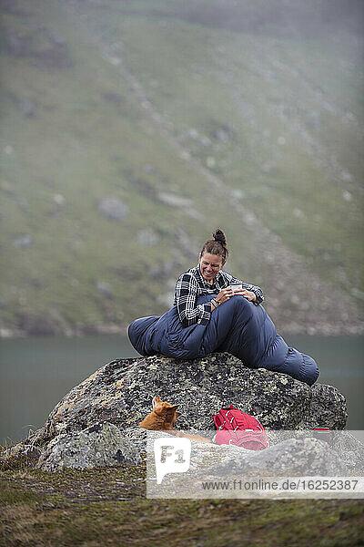 Frau im Schlafsack am See